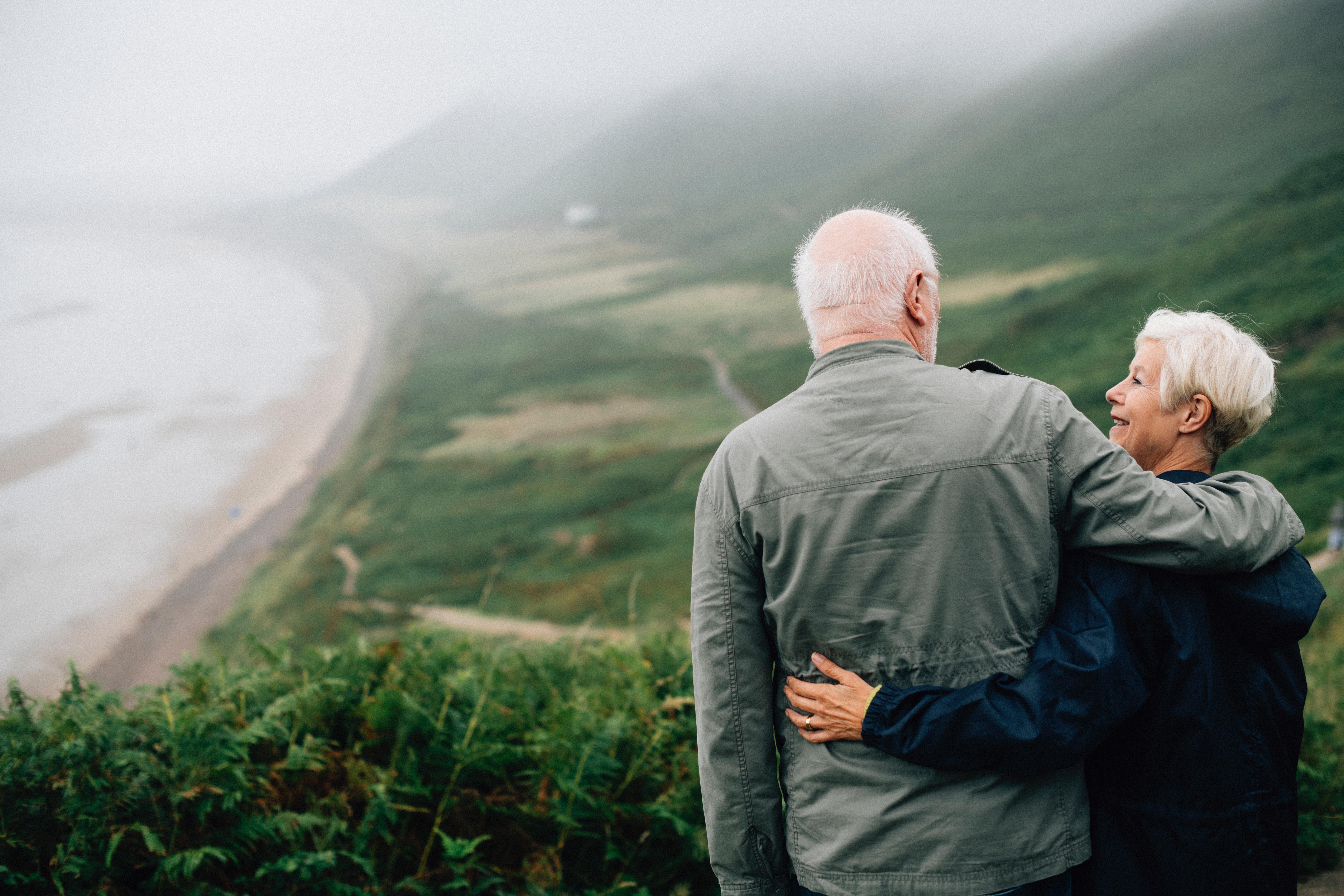 Couple de personnes âgées admirant la vue sur la mer et les montagnes.