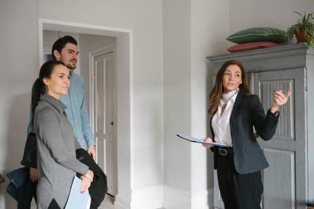 Jeune femme agent immobilier qui fait visiter un appartement à un jeune couple
