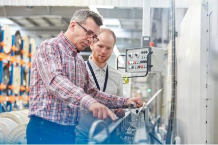 deux hommes qui regardent une machine industrielle