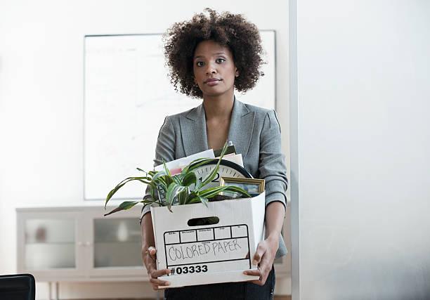 Jeune femme portant un carton avec ses affaires de bureau