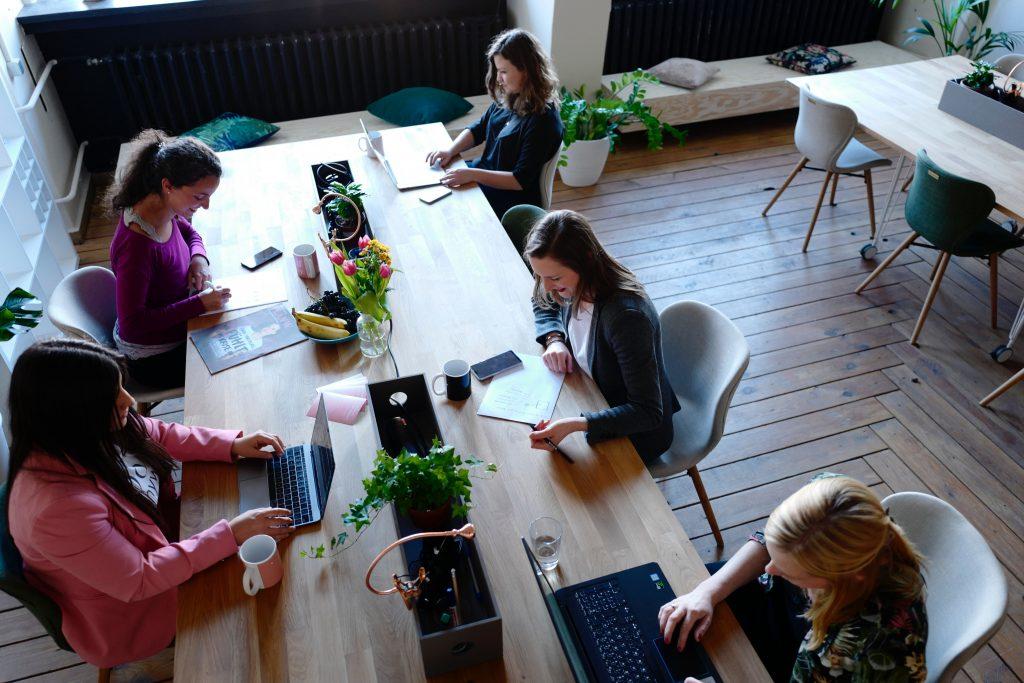 Plusieurs femmes qui travaillent autour d'un bureau partagé