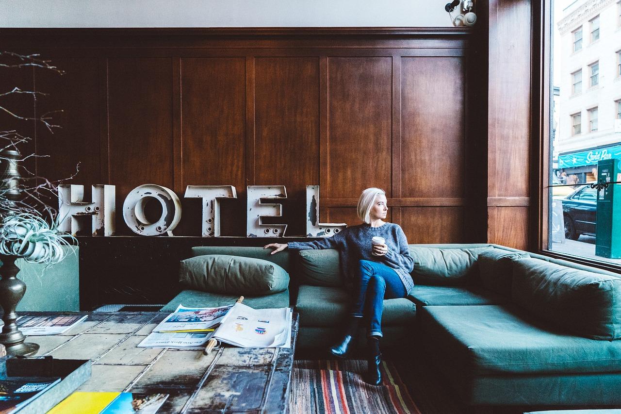 femme assise dans le salon d'un hôtel avec une tasse à la main