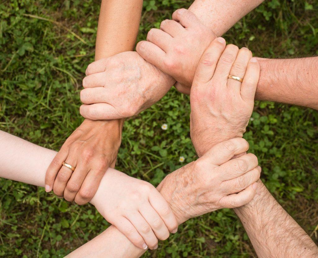 6 personnes qui se tiennent le poignée