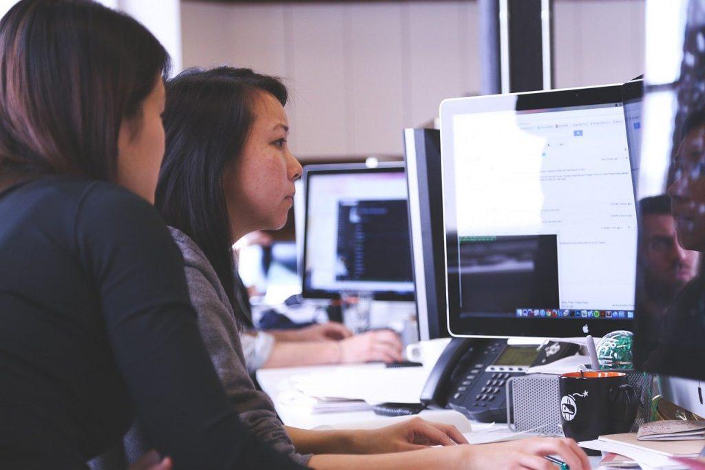 une formatrice et son élève devant un ordinateur