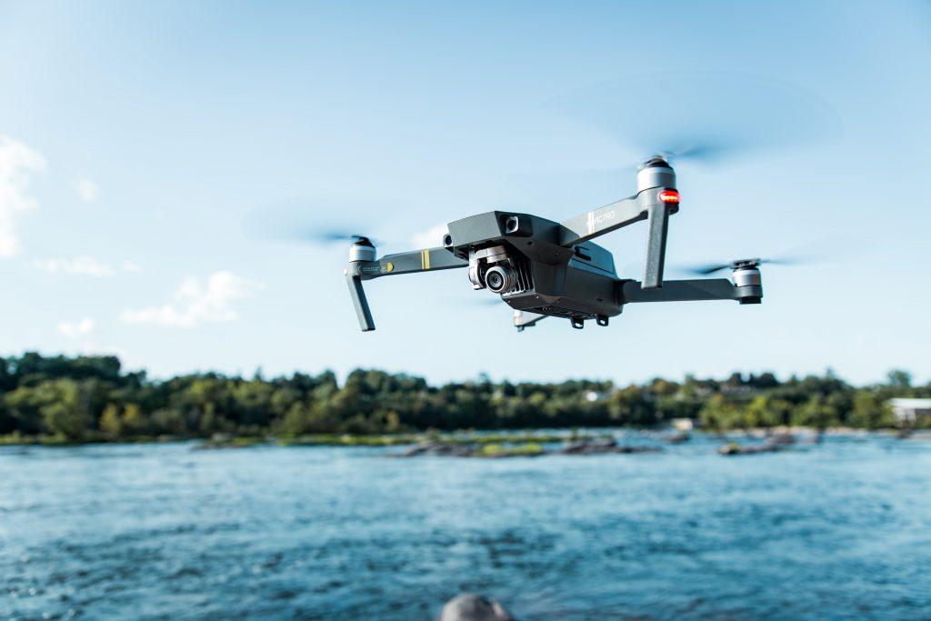 Un drone gris au dessus d'une rivière