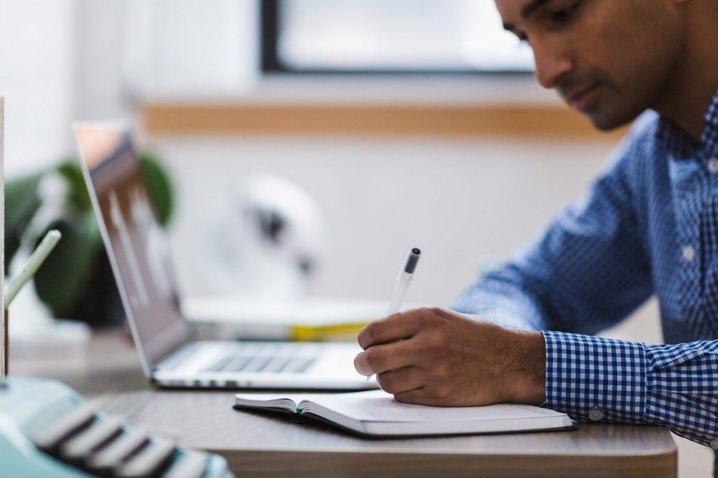 jeune homme qui prend des notes devant son ordinateur