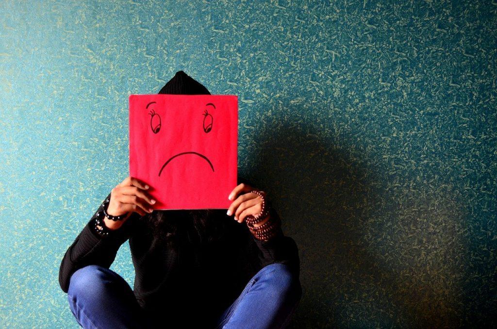 personne qui tient une pancarte rouge sur laquelle il y a un smiley pas content